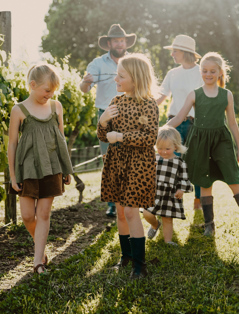 The Maroulis family walking through a vinyard